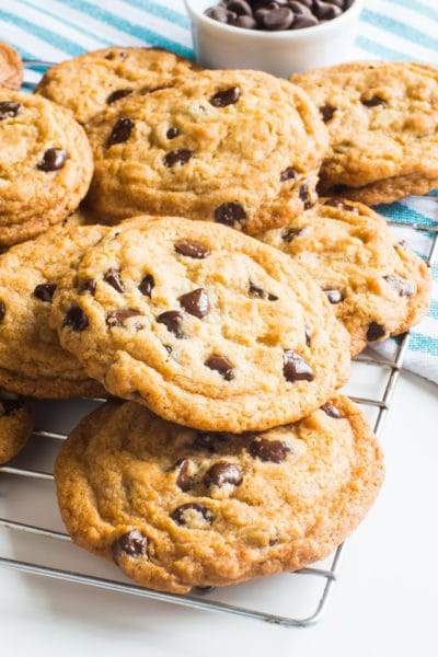 A freshly-baked batch of vegan coconut chocolate chip cookies sit on a wire rack to cool. A bowl of chocolate chips sits behind them.