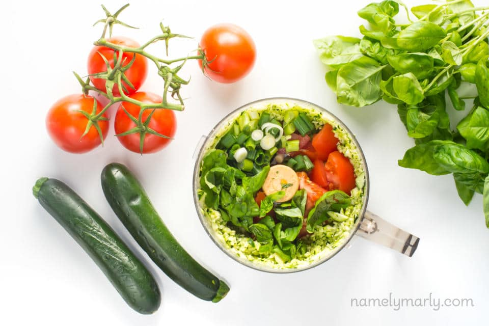 Looking down on ingredients in a food processor next to spinach, zucchini, and tomatoes on the vine.