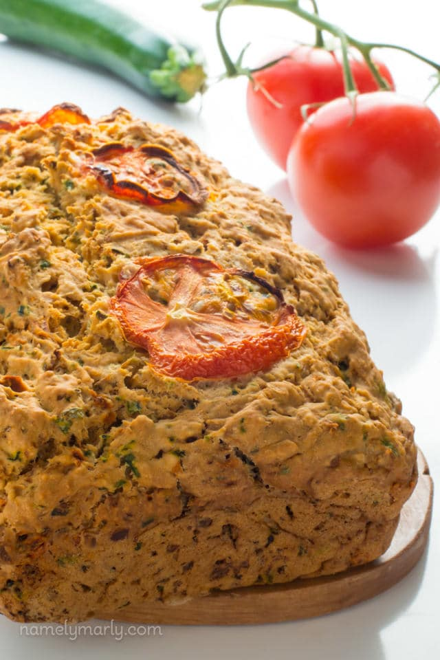 A loaf of savory zucchini bread sits next to tomatoes on the vine and a zucchini.
