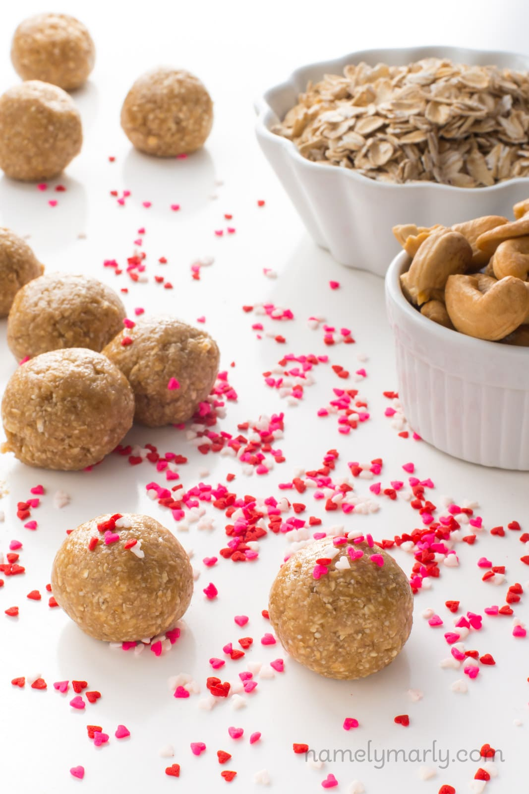 Several sugar cookie energy bites sit on a table. There are pink, red, and white heart-shaped sprinkles all around the table and on some of the energy bites. Beside them are two bowls, one with cashews and one with oatmeal.