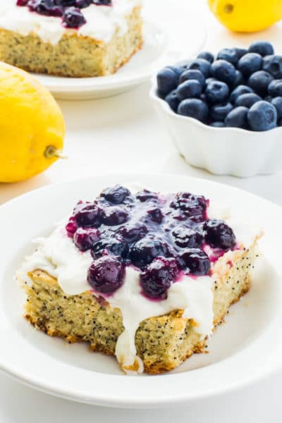 A slice of lemon avocado cake with blueberry sauce on top sits on a plate near lemons, a bowl of blueberries and another slice of cake.