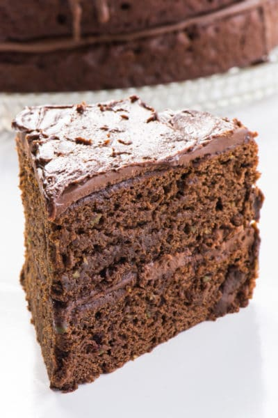 A slice of chocolate cake sits next in front of the rest of the cake.