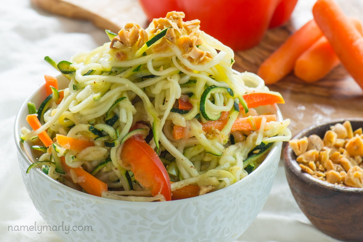 Spicy Vegan Pad Thai Zucchini Noodles are drizzled in a spicy, tangy sauce and topped with chopped peanuts.