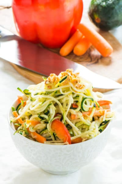 Zucchini Noodles Pad Thai is in a bowl in front of a red bell pepper and other ingredients.