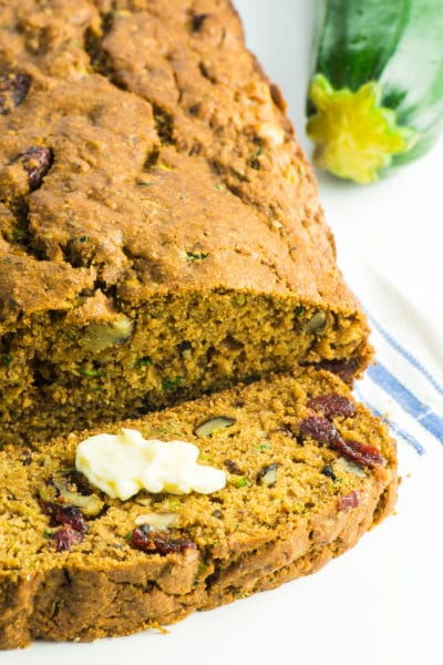 A loaf of vegan healthy zucchini bread with a slice cut off sits next to a zucchini.