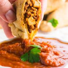 A hand holds a vegan empanada over red sauce.