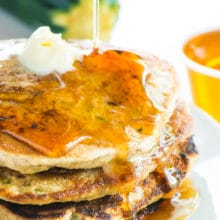 A stack of zucchini pancakes has maple syrup being drizzled over the top. More maple syrup and a zucchini is in the background.