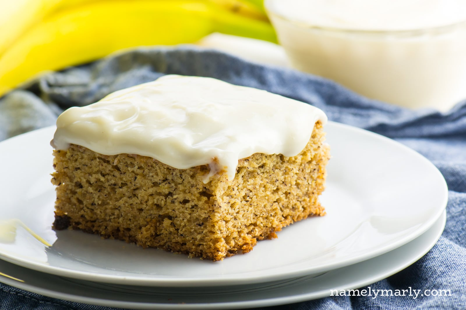 A slice of Vegan Banana Cake sits on a plate in front of bananas.