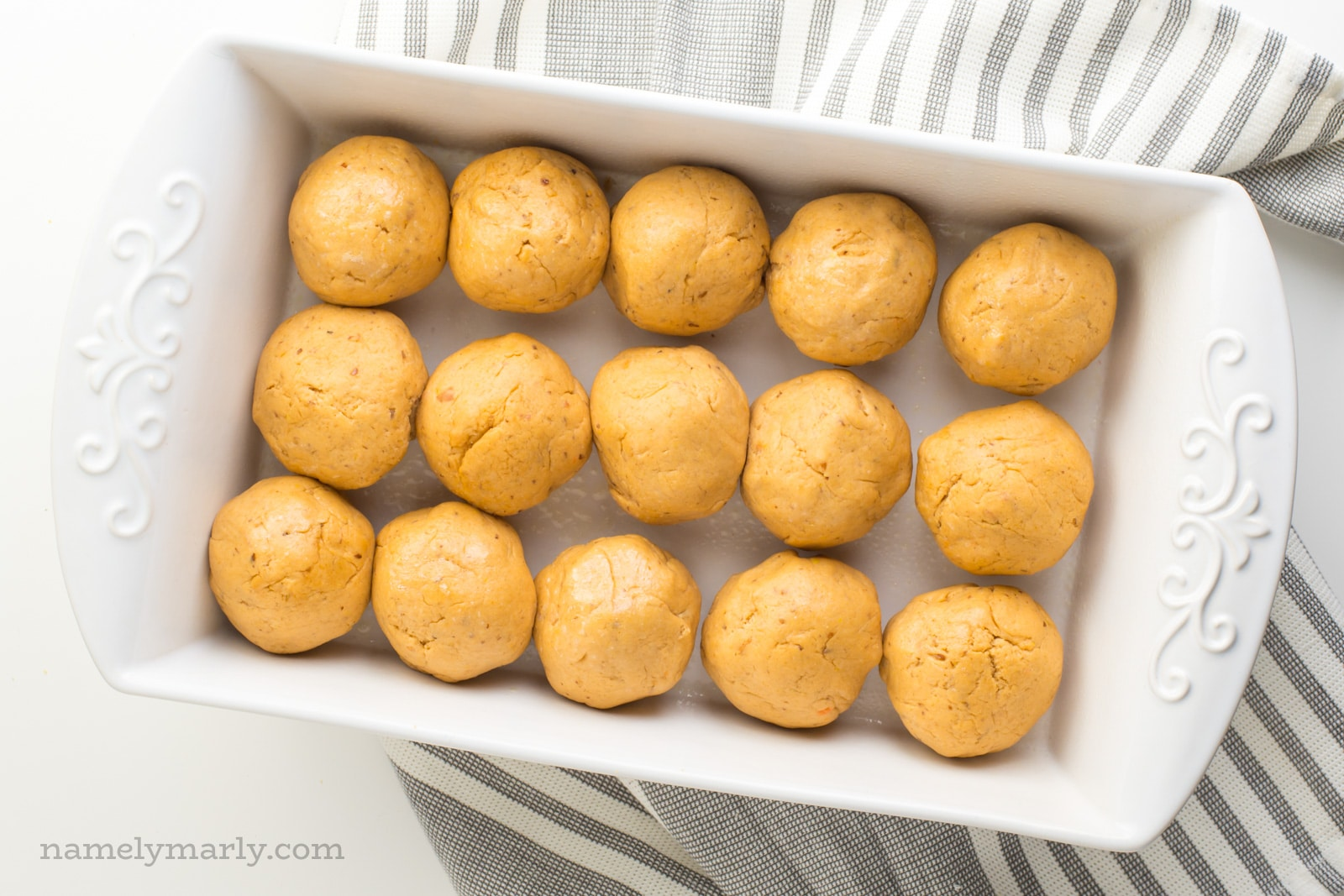 A baking dish full of sweet potato dinner rolls waiting to rise before going in the oven.