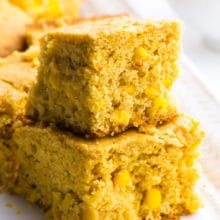 Two slices of vegan cornbread are stacked on top of each other with more slice in the background.