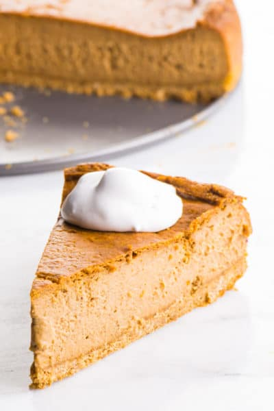 A slice of Vegan Pumpkin Cheesecake is served with vegan whipped cream on top. The rest of the cheesecake is behind it.