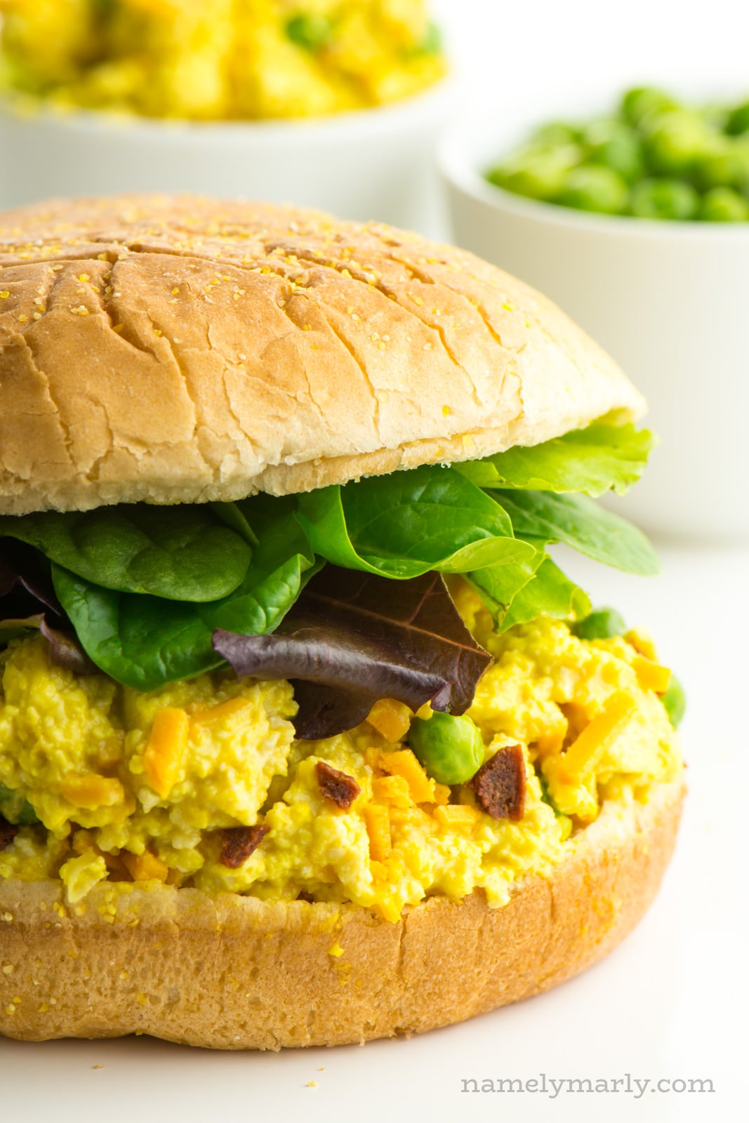 Use this Vegan Seven Layer Egg Salad — made with peas, veggie bacon, and creamy ranch flavors — on your next sandwich to enjoy the delicious flavors of that favorite family dinner salad...in sandwich form! #vegan
