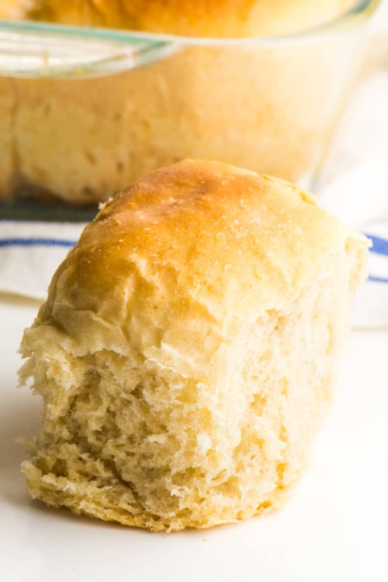 A roll sits in front of a pan of vegan dinner rolls still in the pan.