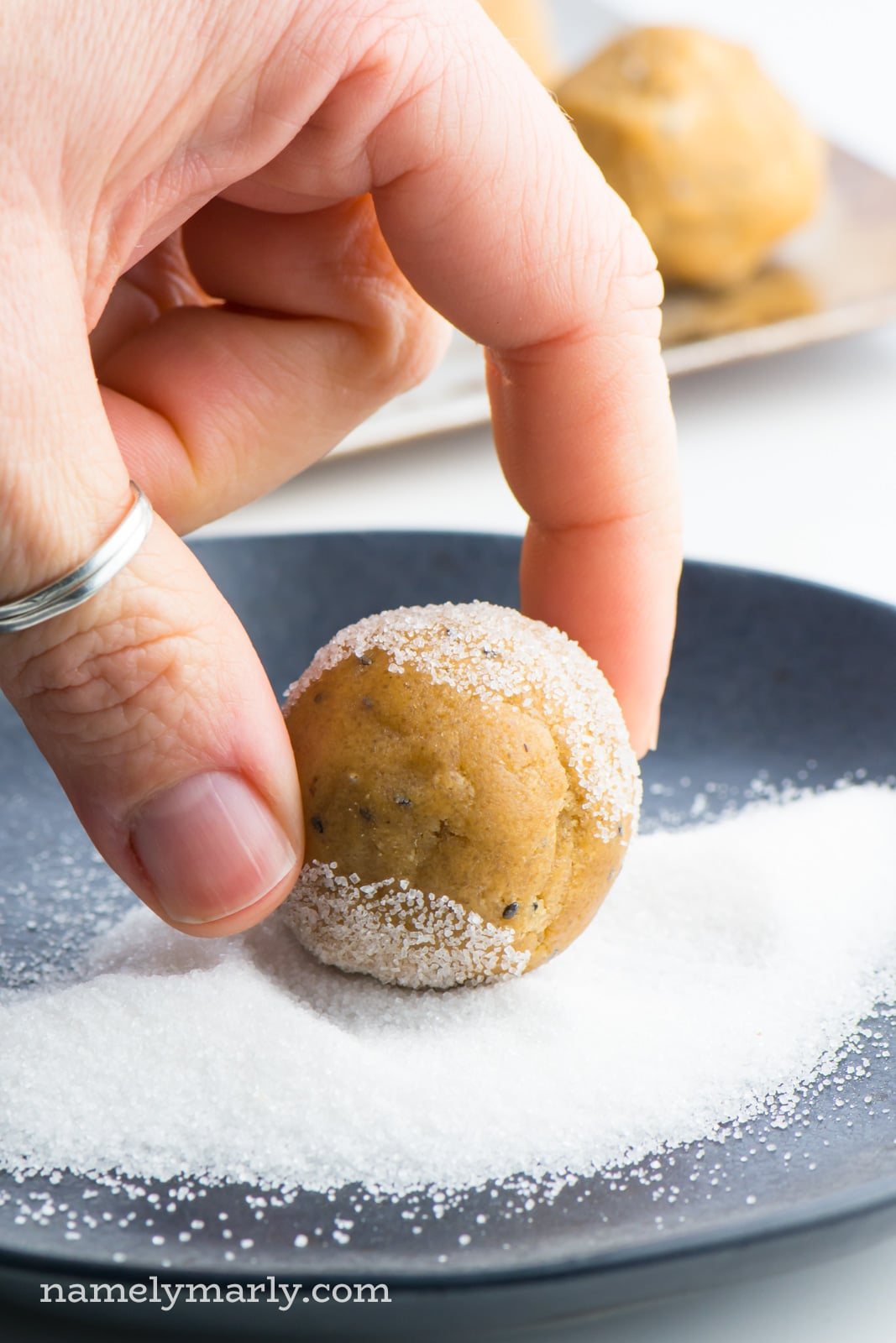 A hand is holding a vegan peanut butter cookie dough ball over a plate of sugar. The cookie dough ball has been partially rolled in the sugar.