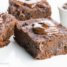 Three slices of chocolate banana brownies sit next to each other, each with a dollop of melted chocolate over the top. A white bowl full of chocolate chips sits nearby.