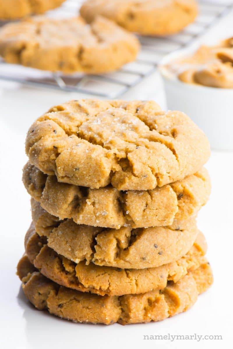 A stack of vegan peanut butter cookies sits in the foreground. Behind them is a white container full of peanut butter and a wire rack with more cookies cooling after being pulled from the oven.
