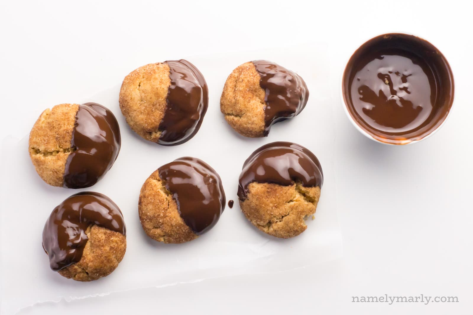 Looking chocolate dipped snickerdoodles with a bowl of melted chocolate beside them.