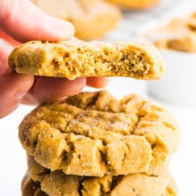A square-cropped image of a stack of vegan peanut butter cookies and a hand holding one with a bite taken out.