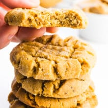 A stack of vegan peanut butter cookies is sitting in the foreground. A hand is holding a cookie right above the stack and there's a bite taken out of that cookie.