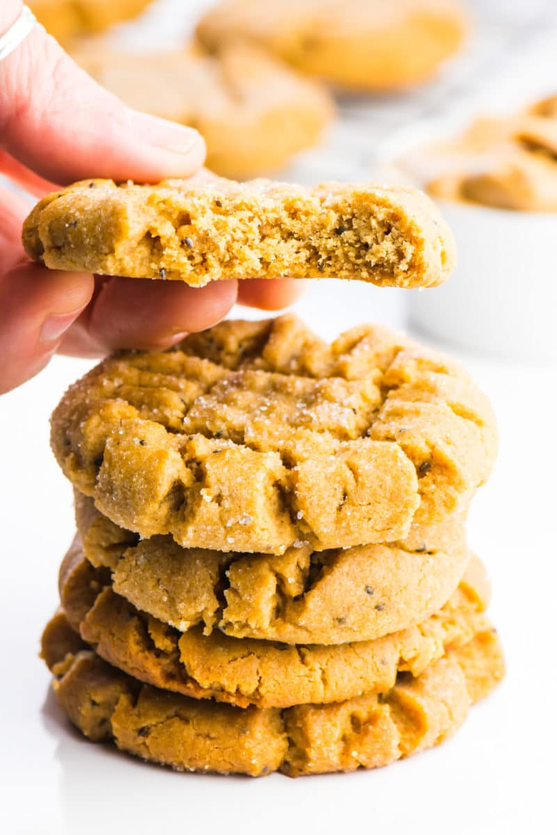 A stack of vegan cookies is sitting in the foreground. A hand is holding a cookie right above the stack and there's a bite taken out of that cookie.
