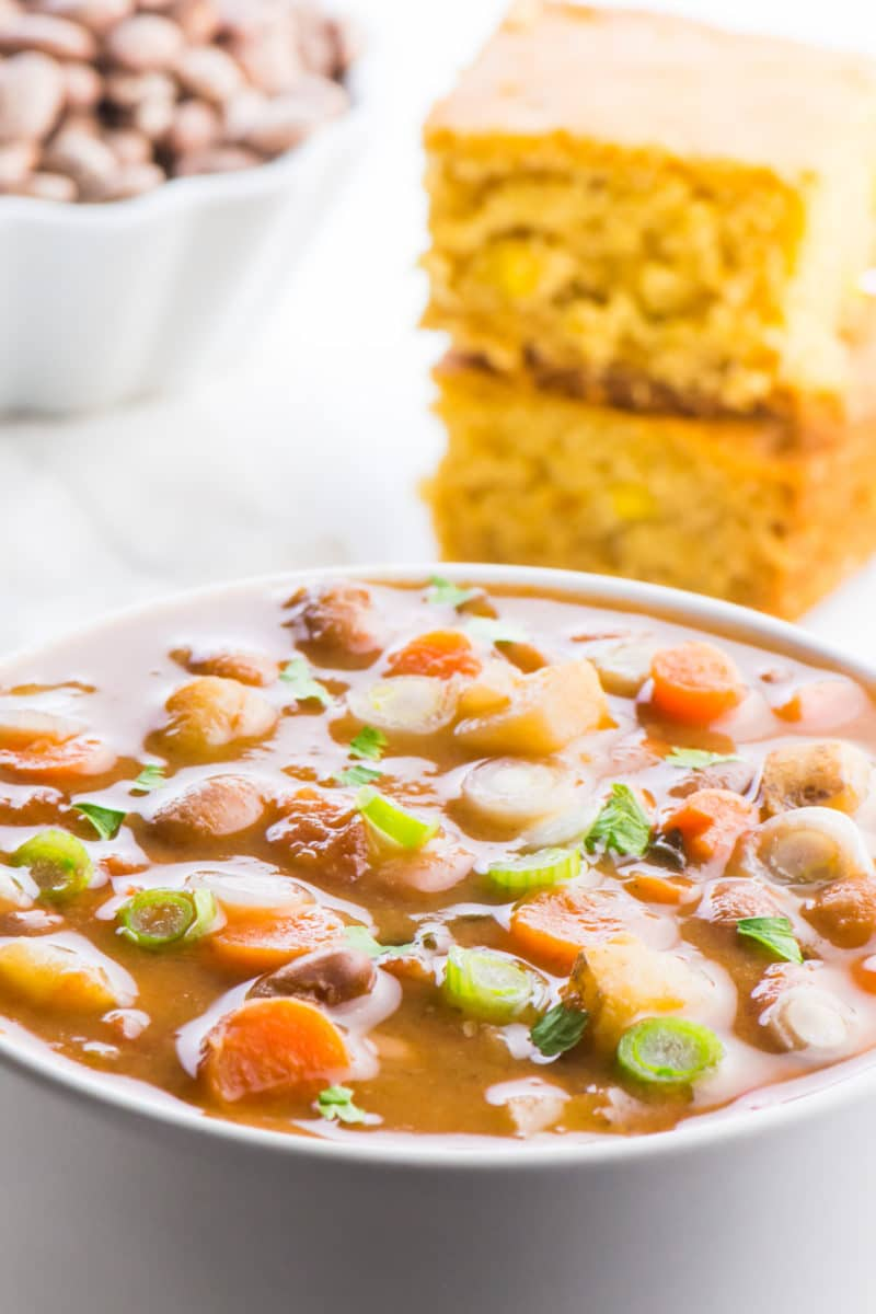 A bowl of pinto bean soup is front in center in this photo. The light is shining on all the ingredients in the bowl, including the slices of carrots, potatoes, and beans. There is a stack of cornbread behind the soup, and a bowl of dried pinto beans behind that.