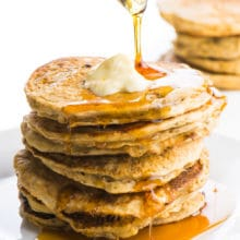 A stack of pancakes without eggs is sitting on a plate. The top one has a pat of melty vegan butter. A glass pitcher is pouring maple syrup and it is dropping down the sides of the pancakes. There are more pancakes in the background.