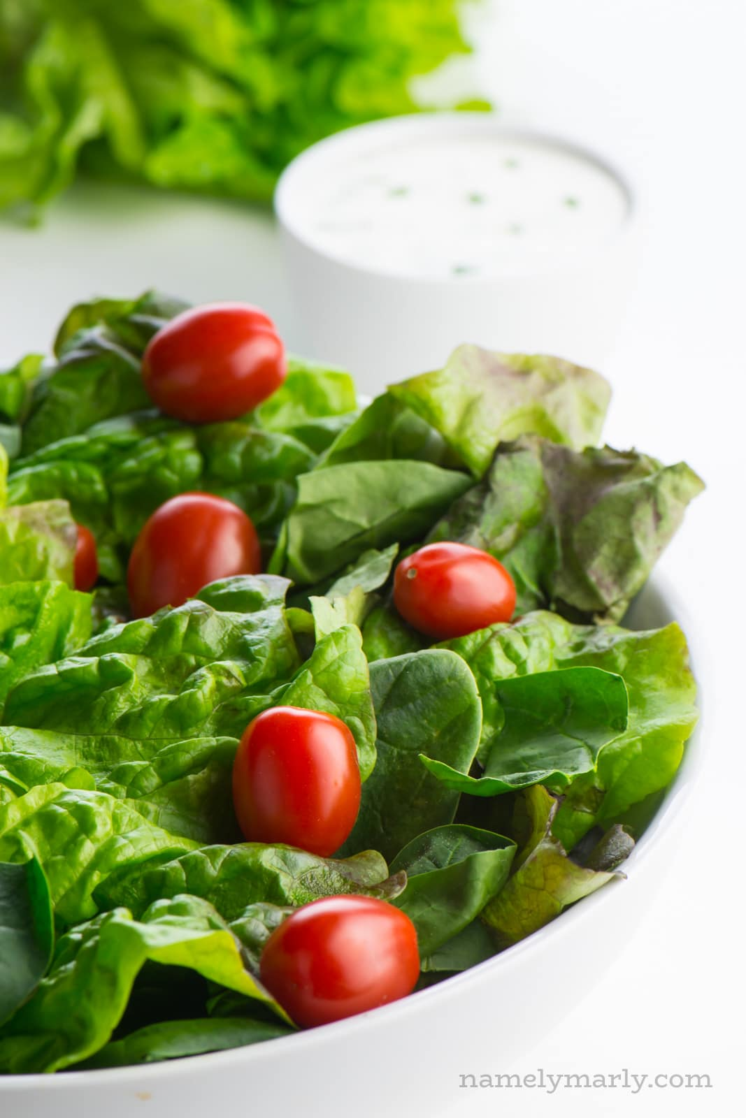 A white bowl full of bright, leafy greens sits in the foreground. A bowl of dressing is behind it.