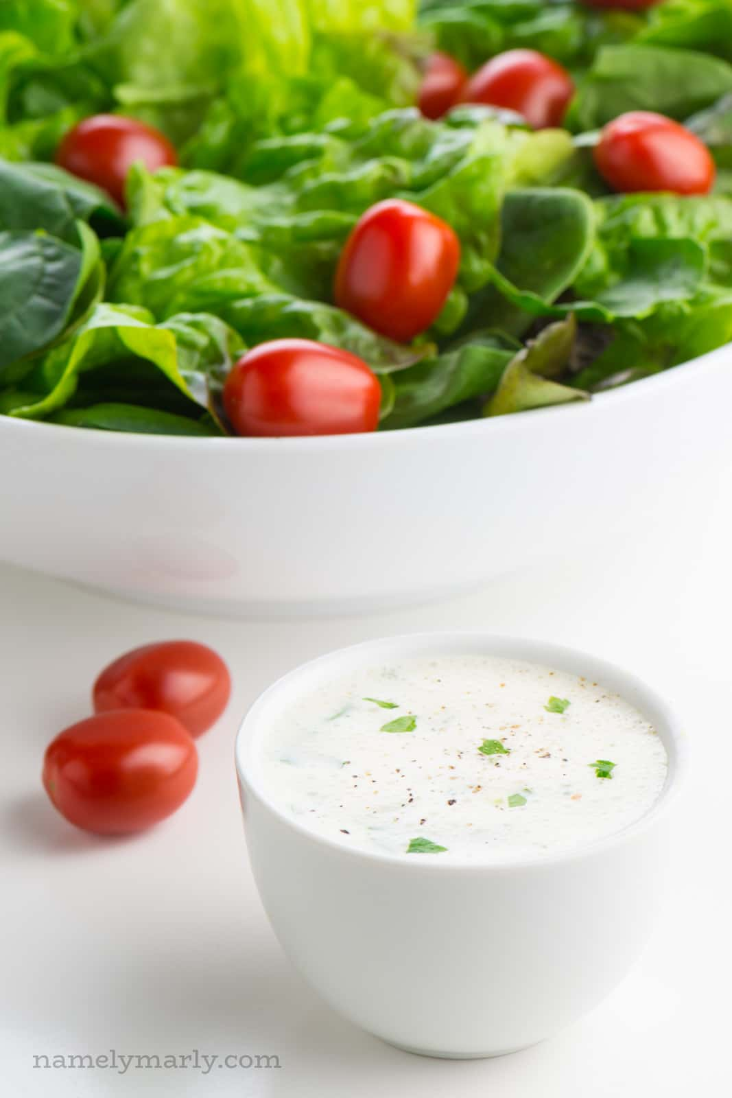 A bowl of vegan ranch dressing sits in front of a salad bowl full of greens and cherry tomatoes.