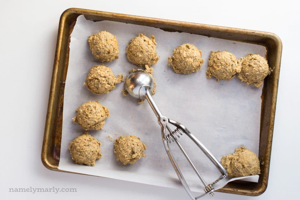 """Uncooked lentil burger """"meatballs"""" on a baking sheet with a cookie dough dispenser used to form them."""