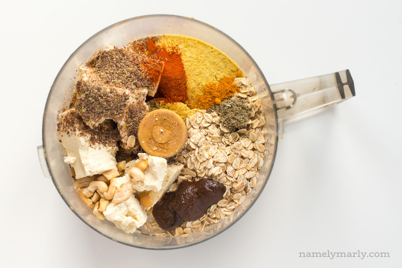 Looking down at a bowl of a food processor with ingredients in it, including oatmeal, tofu, spices, and more.