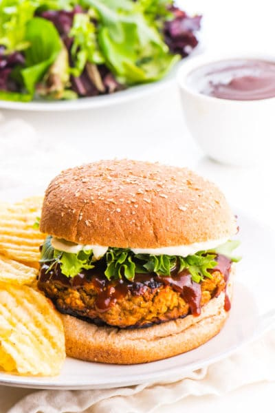 A lentil burger sits on a plate with potato chips beside it. A bowl of sauce and salad greens are behind it.