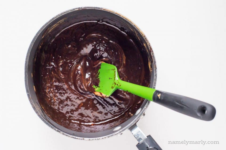 A saucepan is full of chocolate batter. A green spatula is stirring the ingredients.