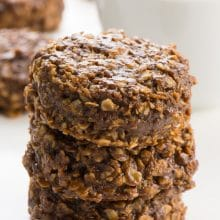 A stack of no bake chocolate chip cookies sit in front of more cookies in the background and a bowl of oats.