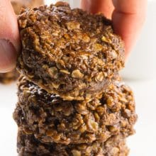 A hand reaches in and grabs a chocolate no bake cookie from the top of a stack of three.