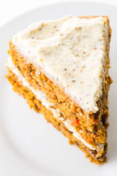Looking down on a slice of healthy carrot cake sitting on a white plate.