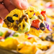 A hand reaches in with a baked vegan nacho taken from the pan behind it.