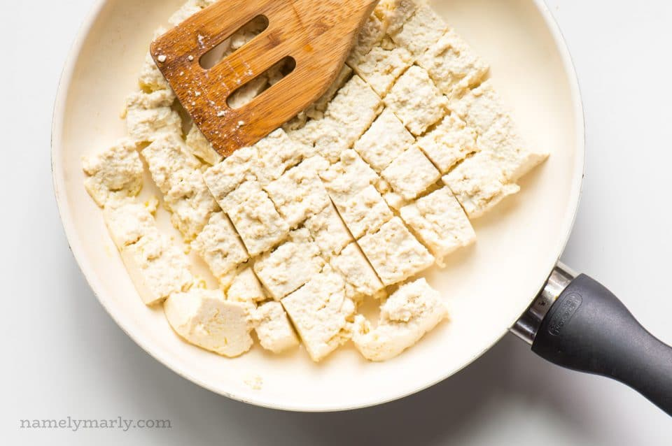 Tofu is in a skillet and it's broken into pieces by a wooden spatula.