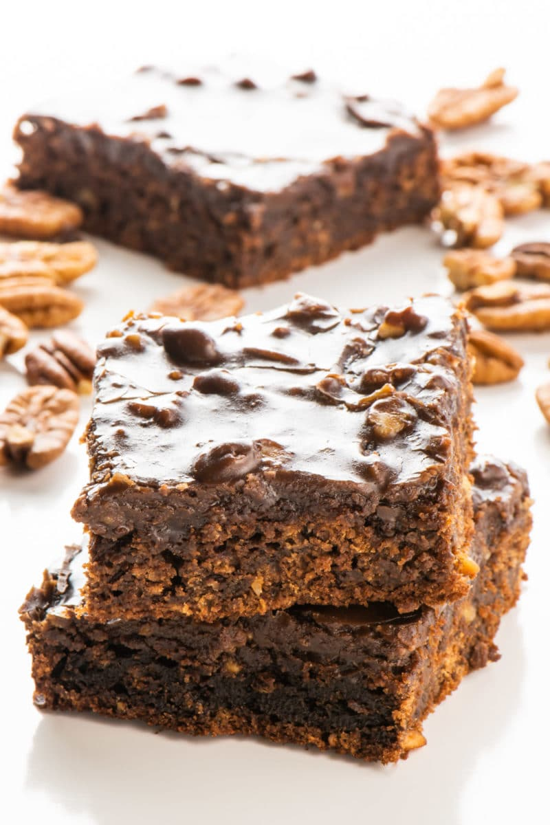 Slices of vegan Texas sheet cake are stacked on top of each other with more slices and pecans around it.