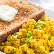 A piece of toast with a pat of melty vegan margarine sits behind a serving of tofu scramble.