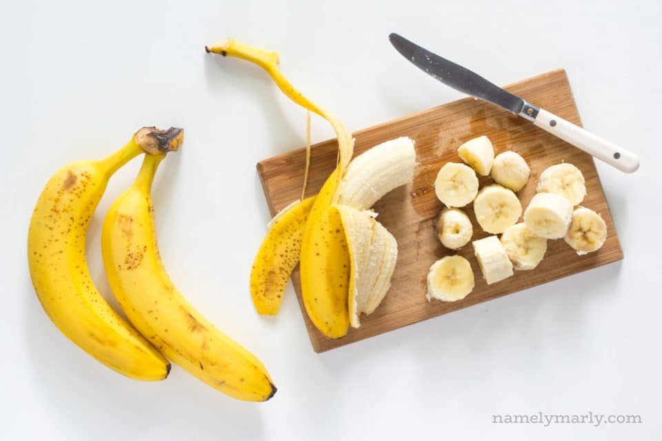 A banana on a cutting board with several chopped bananas next to it.