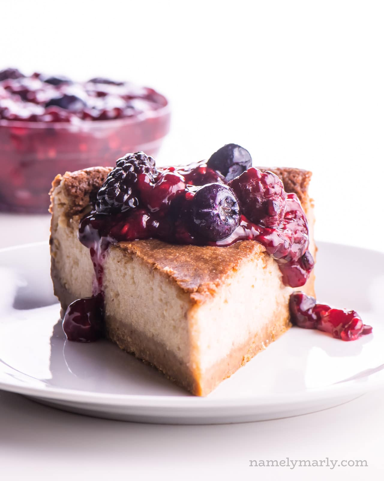 A slice of dairy free cheesecake with berry drizzle over the top and more berry topping in a bowl behind it.