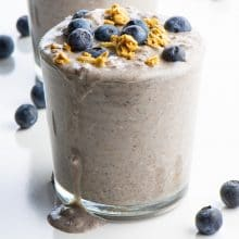 The glass of overnight oats is topped with fresh blueberries and granola.