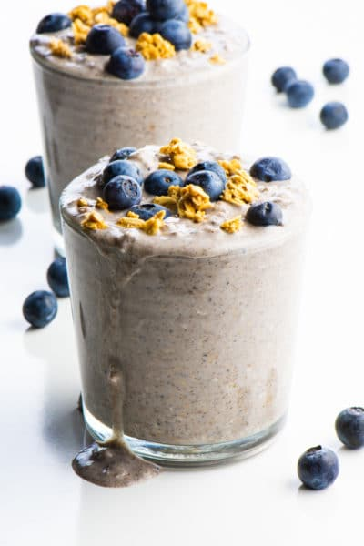 The blueberry overnight oats is in a glass and oozing over the side.