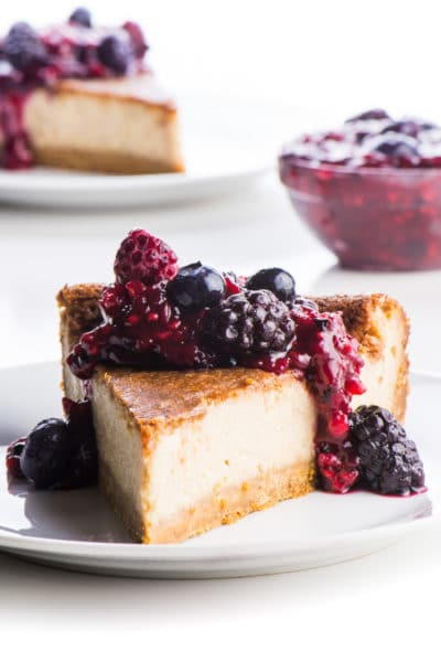 A slice of dairy free cheesecake sits on a white plate with berry sauce drizzled over the top.
