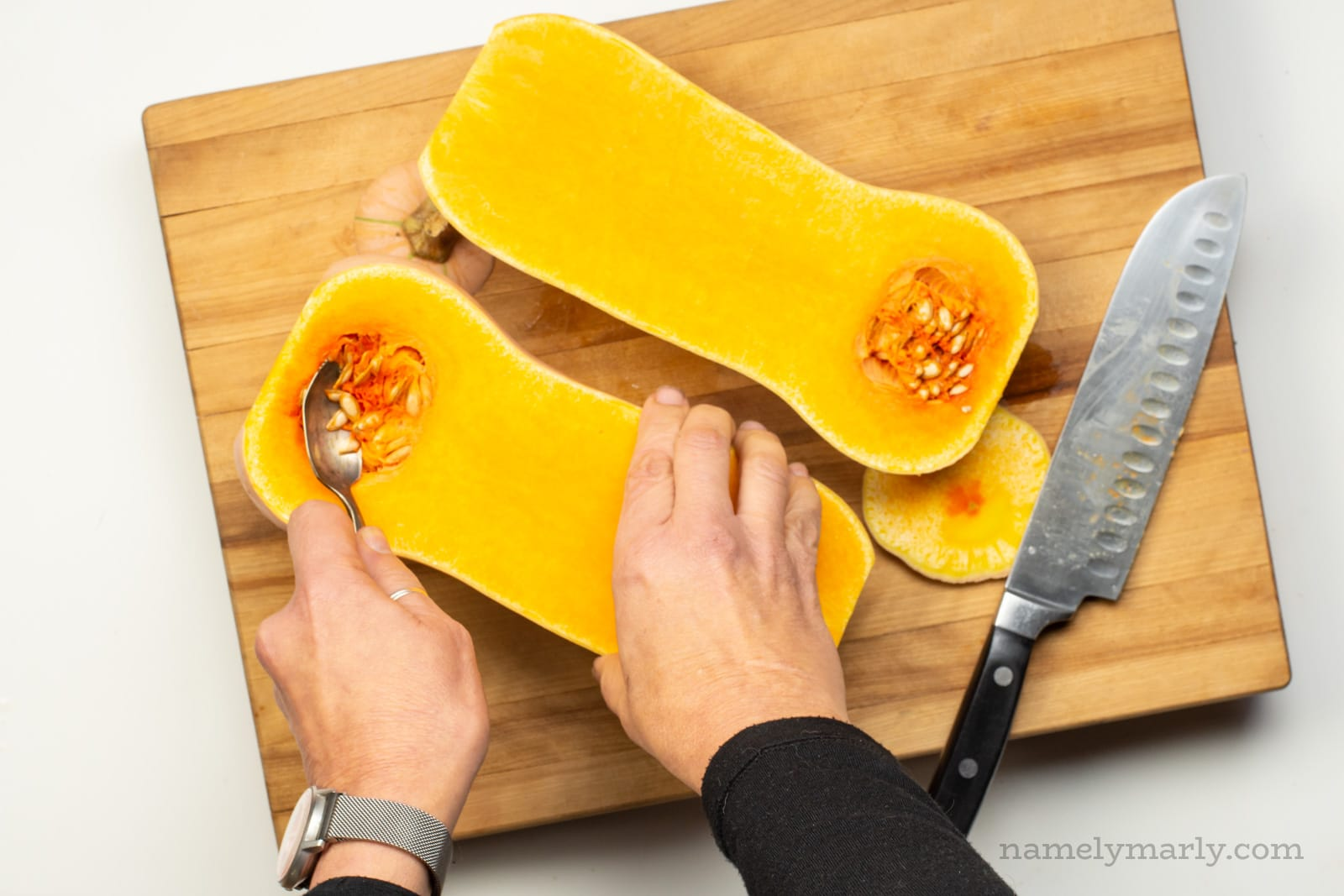 Using a spoon to scoop out seeds from a butternut squash.