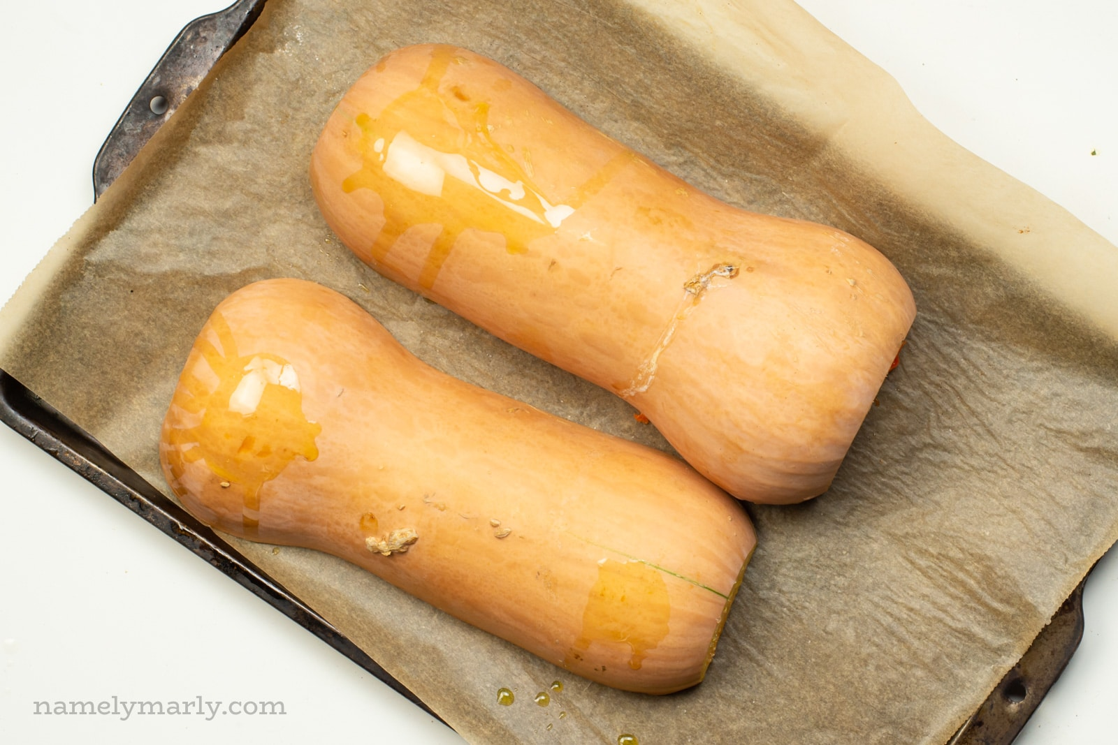 Butternut squash are placed cut side down on a baking sheet.