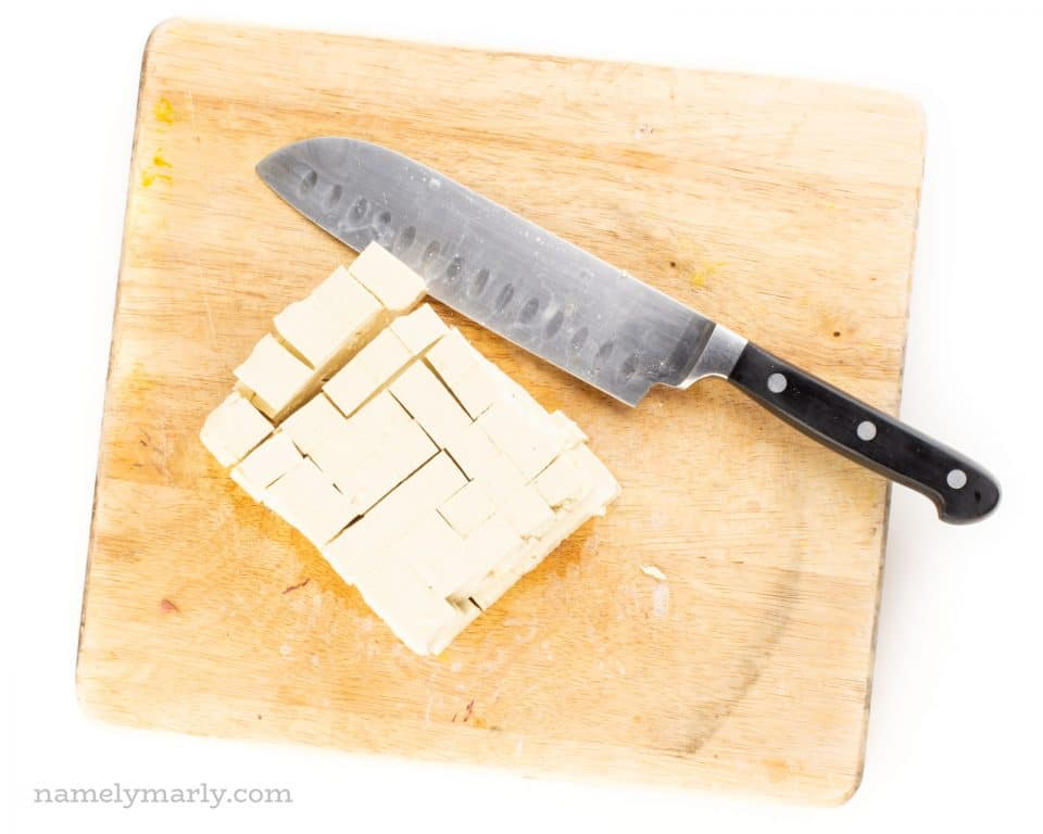 A block of tofu on a cutting board after being sliced into cubes.