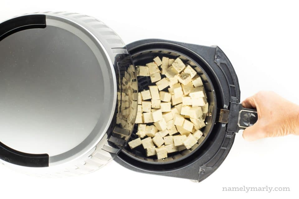 Tofu cubes are in an air fryer basket.