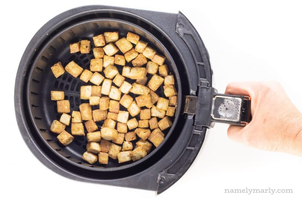 A hand holds the handle of an air fryer basket, full of a fresh batch of air fryer tofu.