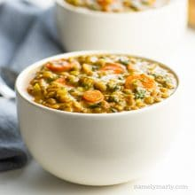 A bowl of curried lentil soup shows chopped carrots and spinach in the bowl.